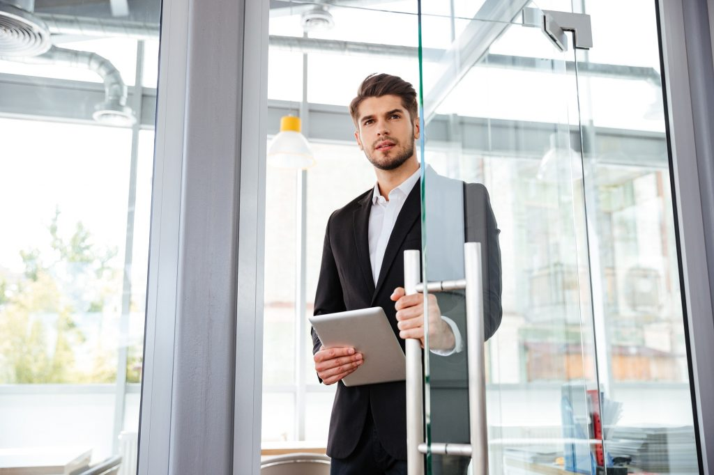 Businesman with tablet entering the door in office